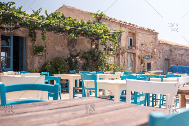 Wooden tables in composition with white and blue chairs on cafe terrace against exteriors of ancient buildings decorated potted flowers and climbing green vine in sunny day
