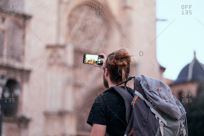 Back view of traveling man with backpack standing on street and taking pictures of historic building during sightseeing
