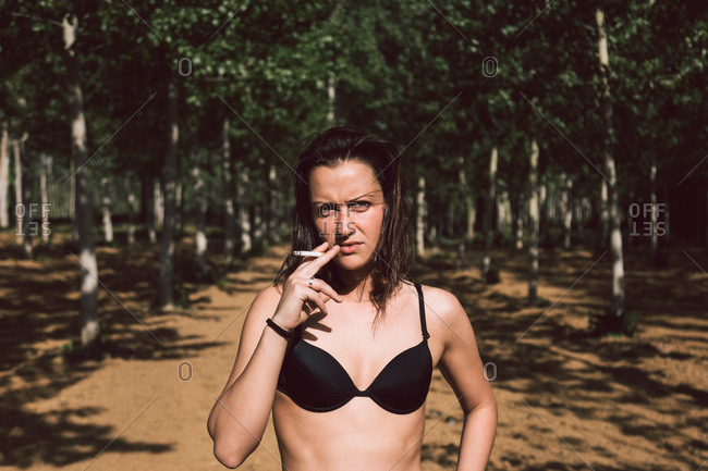 Provocative female wearing black underwear bra smoking cigarette while standing on blurred background of green park and looking at camera during summer day