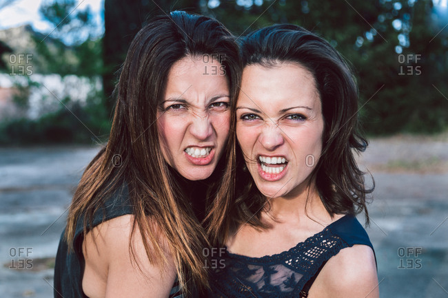 Female lovers standing together in green park and looking with aggression at camera expressing independence and ability to protect each other