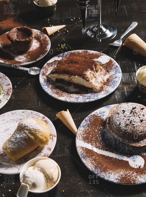 High angle of Tiramisu garnished with cocoa powder placed on table with muffin and chocolate cake sprinkled with powdered sugar