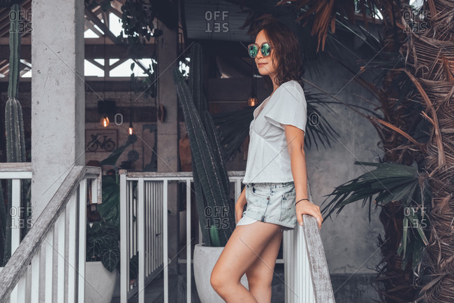 Low angle side view of happy slim female in gray casual shirt and shorts with smartphone touching sunglasses and looking away with interest while leaning on railing at wooden staircase in comfortable resort hotel on Bali