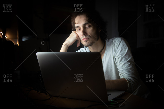 Concentrated young male remote specialist in casual wear talking on mobile phone and using laptop while working on project in dark room at home during evening time