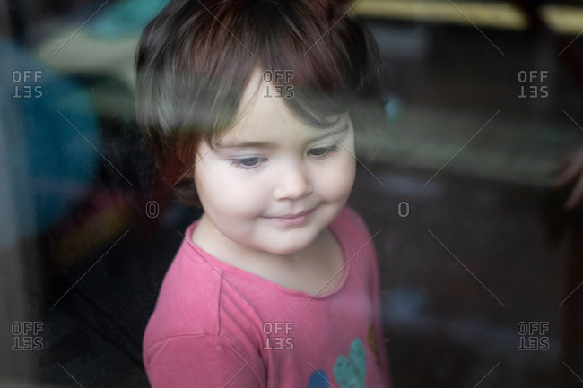 Side view of little girl standing near window and looking out while spending time at home