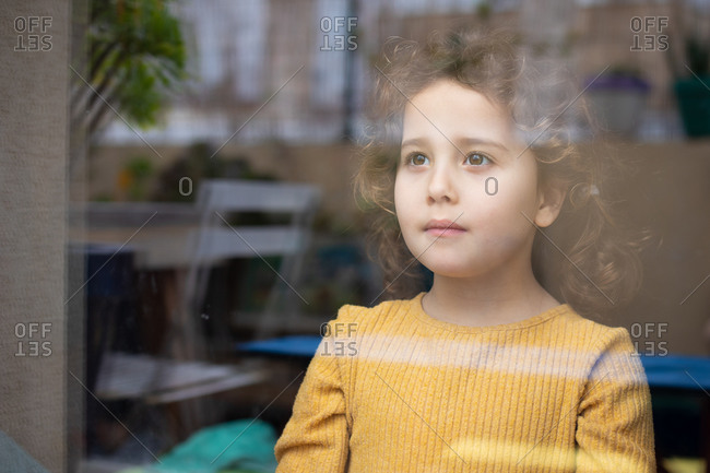 Calm little girl with curly hair standing near window and looking away thoughtfully while spending time at home and dreaming about adventures