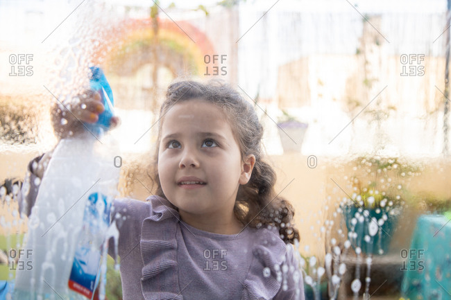 Positive little girl in casual dress with spray bottle of cleanse washing glass in room with rainbow painted on window during coronavirus quarantine