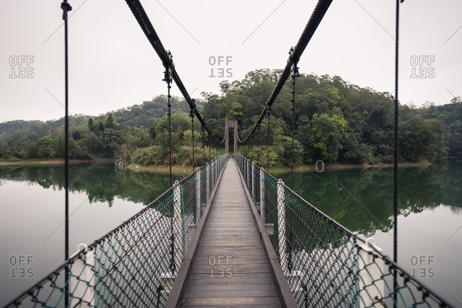 Suspension bridge with wooden floor and metallic grid over large lake and vast green forest under white sky in afternoon