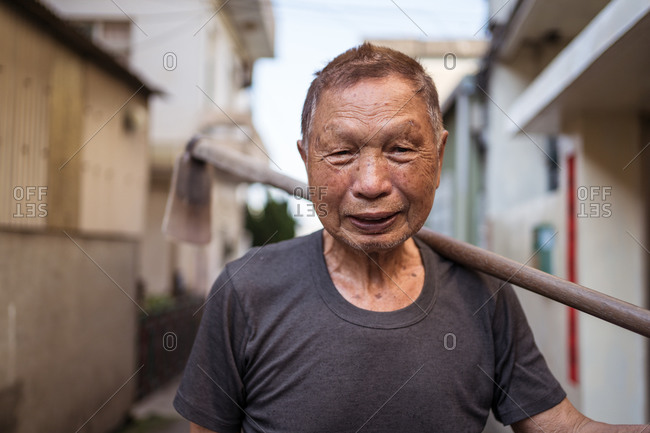Portrait of elderly Asian male gardener in casual clothes smiling at camera while standing on street with hoe over shoulder in settlement in Taiwan