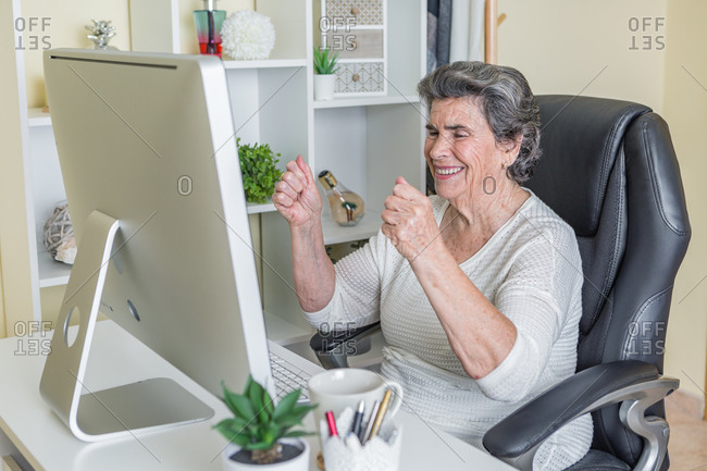 Excited elderly lady in casual clothes sitting in armchair at table and raising hands up celebrating great news while watching computer at home
