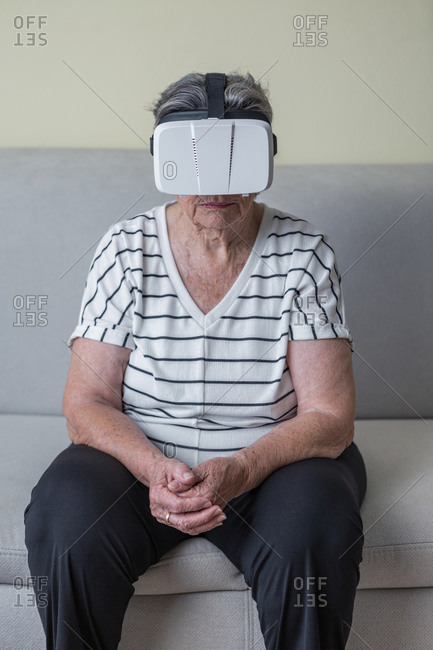 Amazed senior woman in casual clothes wearing goggles of virtual reality exploring another world holding hands up while standing in living room at home