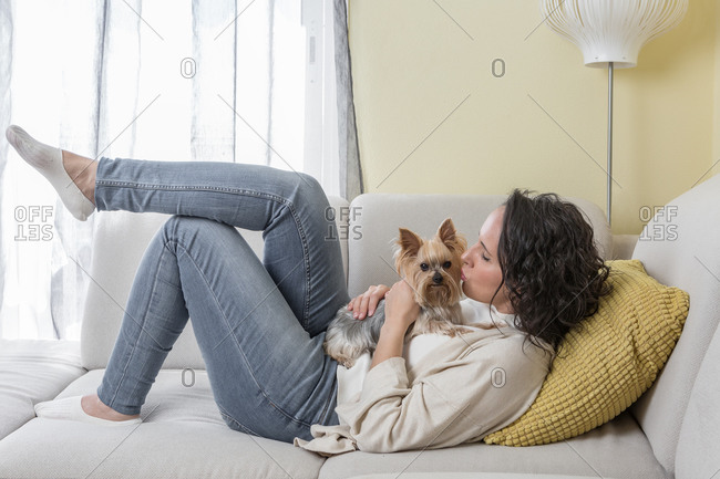 Side view of positive woman in casual clothes kissing Yorkshire terrier dog while resting on comfortable sofa in living room at home