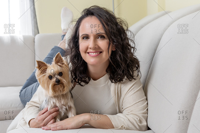 Positive woman in casual clothes kissing Yorkshire terrier dog while resting on comfortable sofa in living room at home