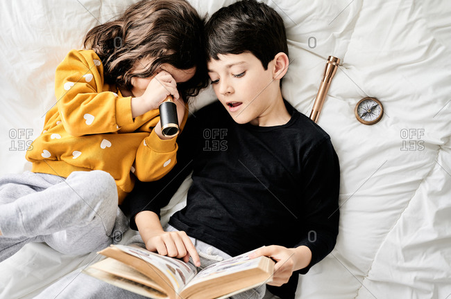 From above of brother reading book and sister playing with retro spyglass relaxing on comfortable bed and enjoying weekend