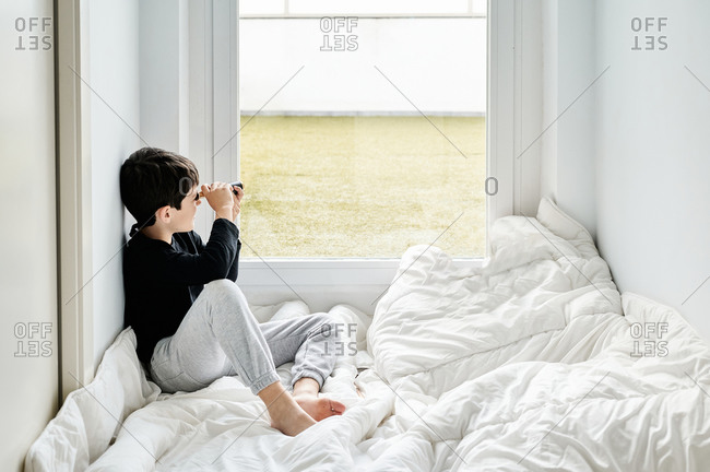 Side view of calm child wearing casual clothing sitting on cozy white blanket in hall and playing with vintage spyglass while looking out of window