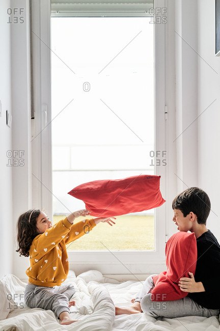 Side view of friendly brother and sister sitting on cozy blanket near window and playing with soft pillows while having fun during weekend