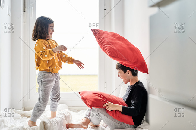 Side view of friendly brother and sister standing on cozy blanket near window and playing with soft pillows while having fun during weekend