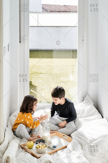 Cheerful kids in pajamas sitting with crossed legs near tray with healthy food while taking glass of milk on breakfast in morning