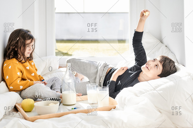 Smiling brother and sister in casual clothes sitting on soft white blanket near window in hall with breakfast tray and sharing food in morning