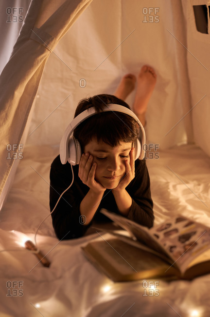 Thoughtful male child in headset reading book with images while listening to music and lying in cozy kids play tent in apartment