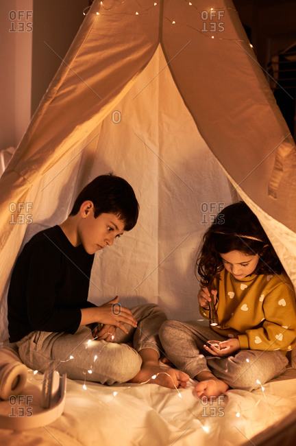 Curios boy watching sitting near dreamy little sister in casual wear playing with flashlight in garland tent in evening in flat