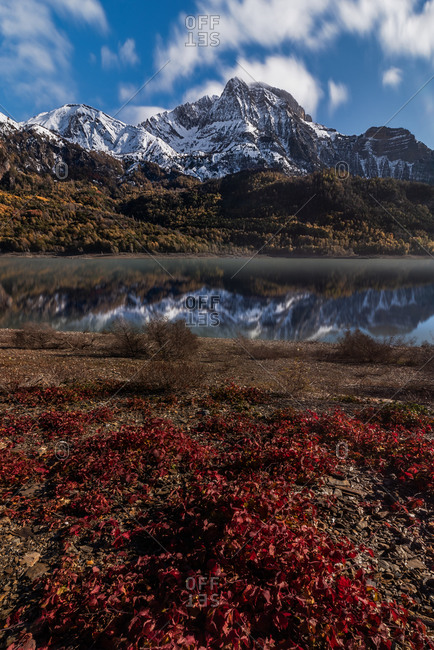 Peaceful view of snowy mountain valley with bushes growing on slopes and calm pond in evening in autumn