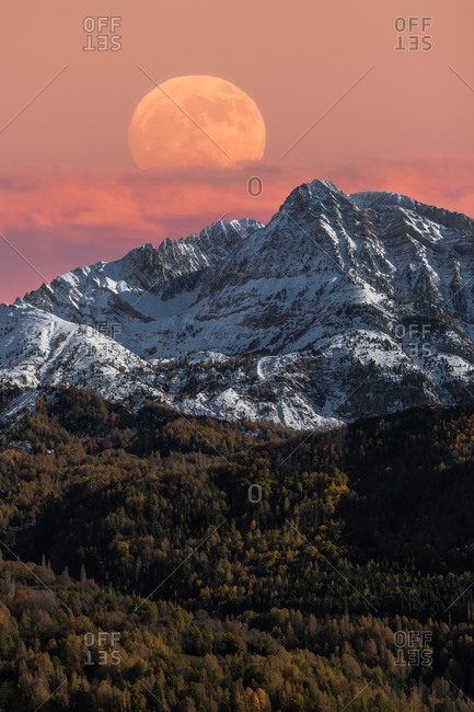 Majestic mountain landscape with full moon in colorful sky over snowy rocky range and dense forest in autumn time