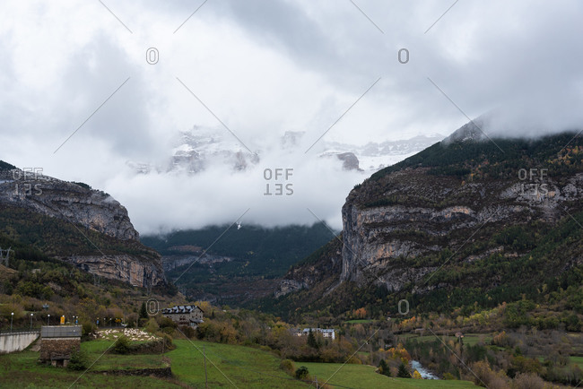 Majestic rocky mountains and green valley with small village houses covered with thick fog and clouds in autumn day