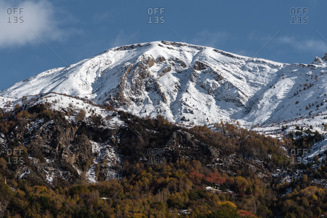 Spectacular landscape of mountain with snowy peak and colorful forest on slope under blue cloudy sky in sunny autumn day