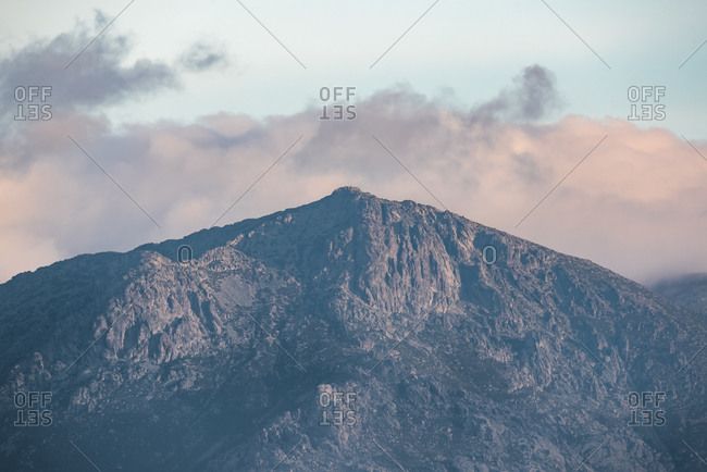 Calm landscape with mountain range covered with fog against cloudy morning sky in autumn season