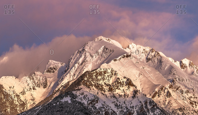Sharp mountain peaks covered partially with snow and surrounded by fog under picturesque cloudy pink and purple sky at nightfall in wintertime