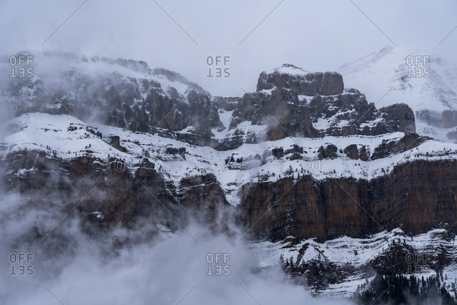 Sharp mountain peaks covered partially with snow surrounded by misty fog under cloudy sky in wintertime