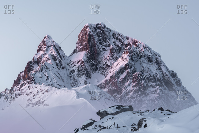 Sharp mountain peaks covered partially with snow under cloudy sky in wintertime