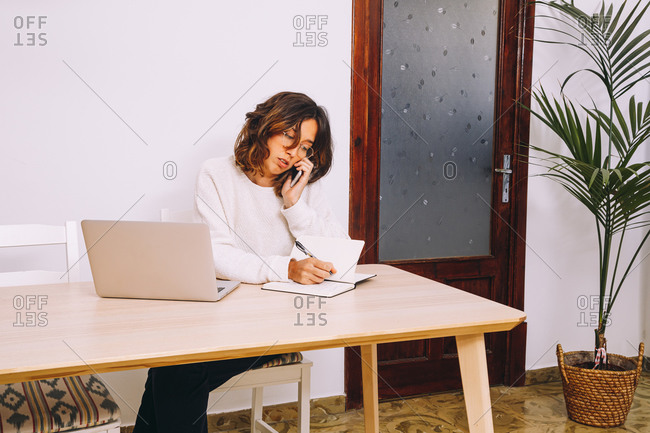 Modern female entrepreneur in casual clothes sitting at table with laptop and taking notes in notebook during phone conversation while working on remote project at home