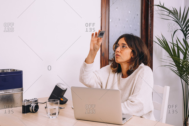 Young female photographer sitting at table with laptop and photo camera with projector and working with old photo slides at home workplace