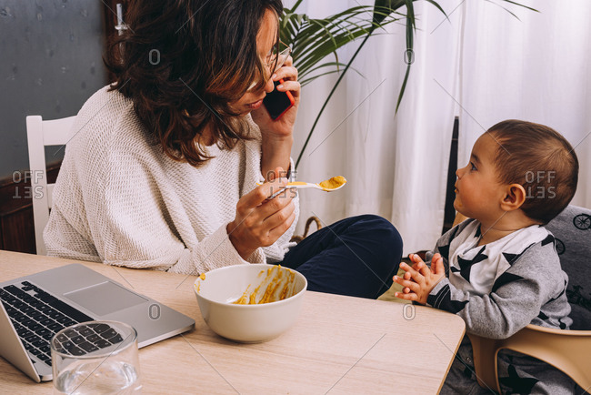 Modern young female remote worker feeding little child and discussing business issues on smartphone while sitting at table with laptop and working on online project