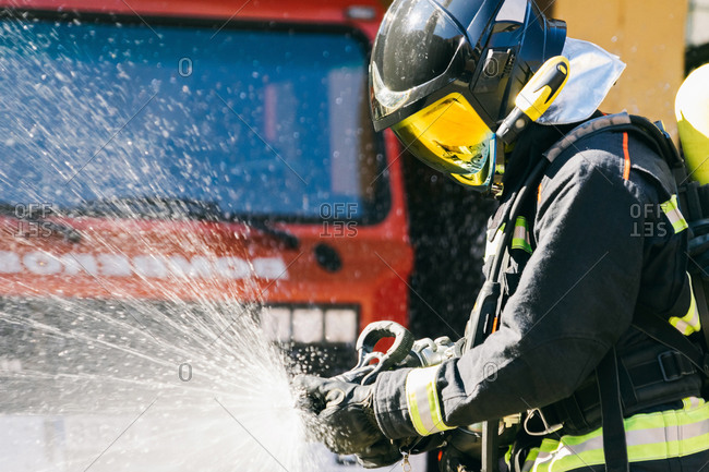 Faceless fireman in safety helmet and protective uniform extinguishing fire with water hose during training on sunny day