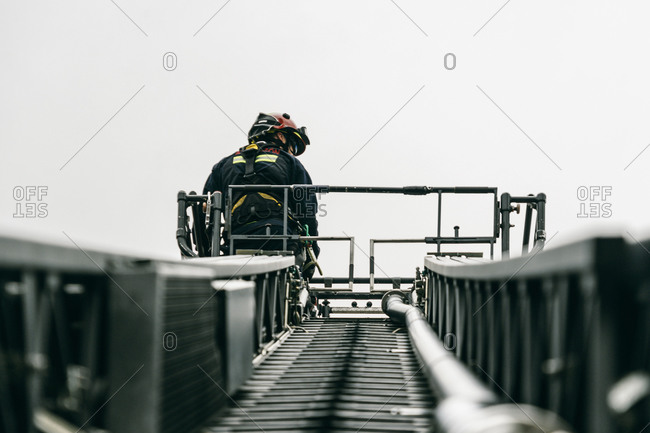 From below of brave fireman standing on aerial platform of fire engine during training on background of gray sky