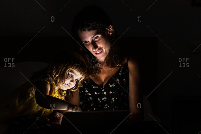 Woman showing tablet to amazed girl while sitting on bed in dark bedroom at home