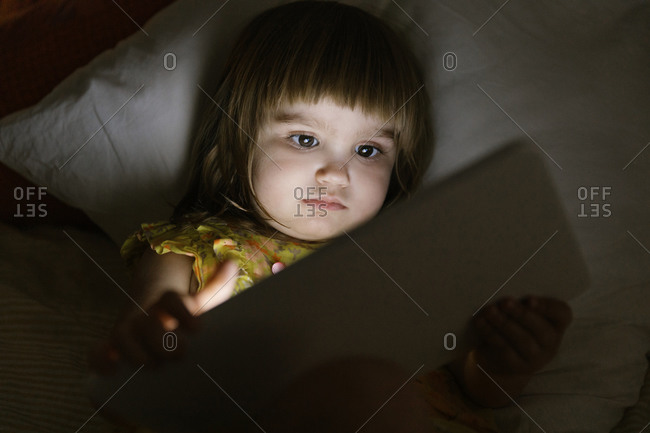Cute little girl playing games on tablet while lying on soft pillow in bed in dark bedroom at night at home