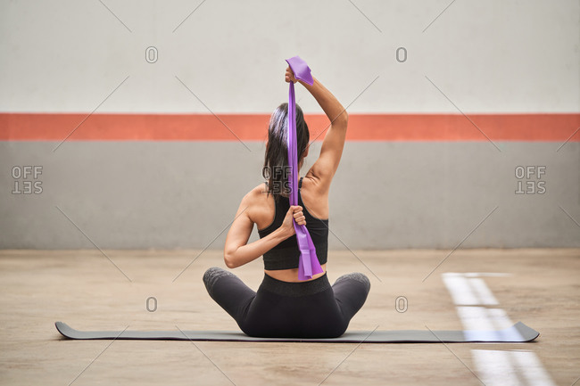 Back view of slim female in sportswear sitting on mat and stretching muscles with elastic band in gym
