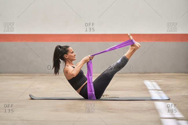 Cheerful athletic female in activewear sitting barefoot on mat and stretching legs with resistance band during training