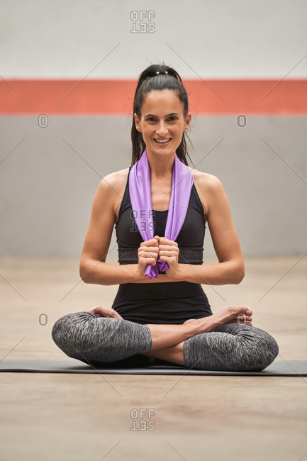 Tranquil female in sportswear sitting on mat with resistance band and looking at camera