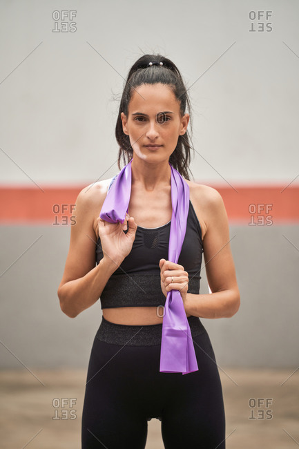 Tranquil female in sportswear standing on mat with resistance band and looking at camera