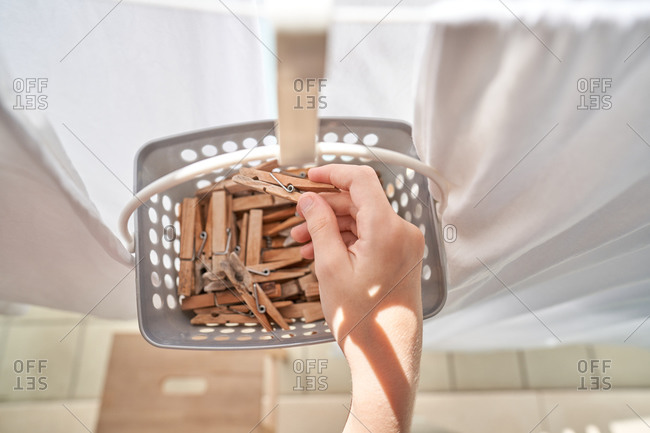 From above anonymous cropped person taking clothes pegs from basket hanging clothes after wash on rope on balcony on sunny day in summer