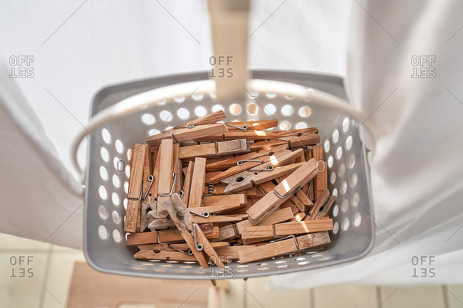 From above clothes pegs inside basket hanging on rope on balcony on sunny day in summer