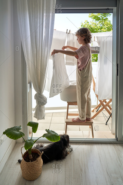 Side view of kid in casual clothes standing on chair on balcony and hanging wet linen on rope with dog lying down on the floor at home
