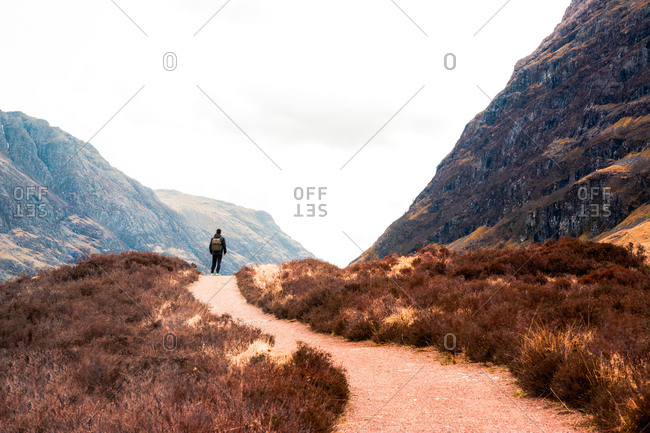 Back view of unrecognizable hiker with backpack standing on trail leading through hills with dry grass and admiring view of mountains against cloudy sky in Scottish Highlands