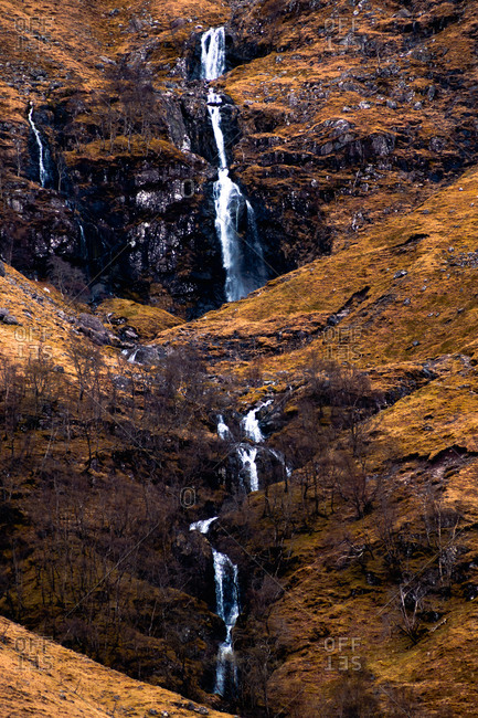 Rough rocky mountain slope with leafless bushes and waterfall in Scottish Highlands