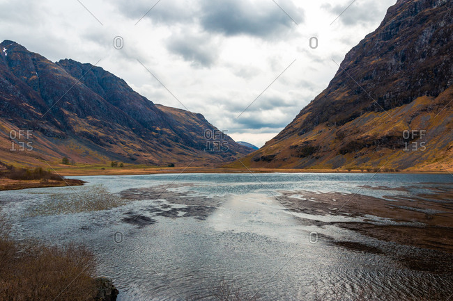 Amazing Scottish landscape of calm lake with mirrored surface reflecting mountain with snow covered peak and blue cloudy sky in Glen Coe area