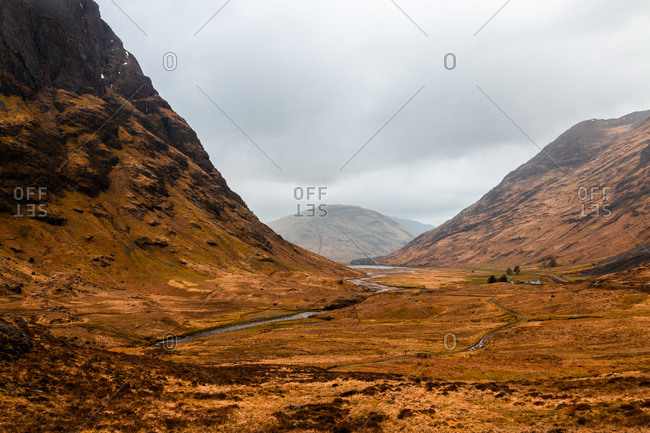 Narrow curvy road running through hilly terrain with dry grass among rocky mountains in cloudy spring day in Scottish Highlands